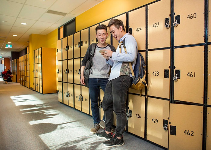 Two Taylors High School students standing by the campus student lockers.