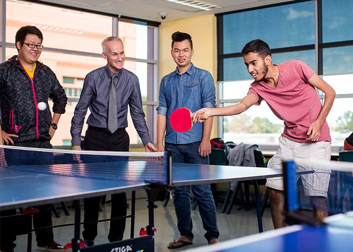 Taylors High School students are in the common room with their teacher playing table tennis.