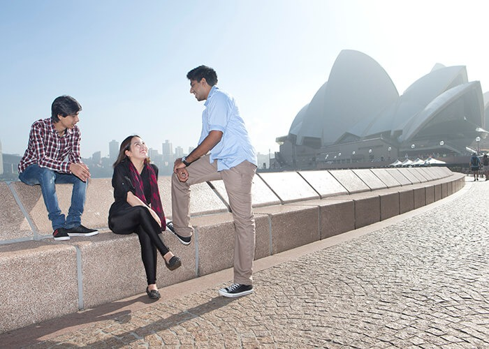 Three Taylors High School studens are standing near the Sydney Opera House.