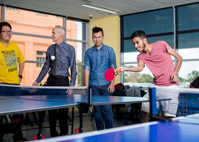 Taylors High School students are playing table tennis with Paul Mahony (Director of Studies TELP)