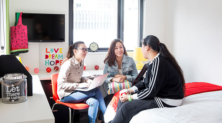 Three female Taylors High School students are having a conversation at the student accommodation.