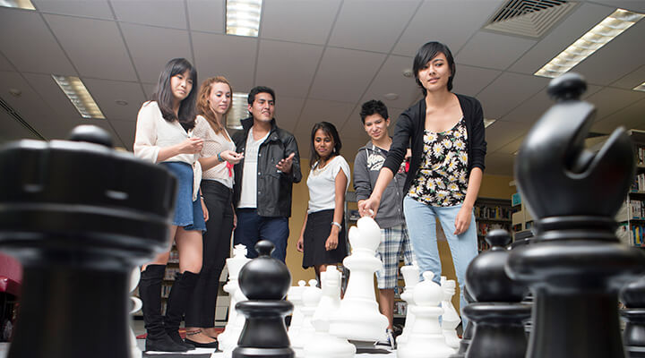 Taylors High School students playing giant chess in the campus library.