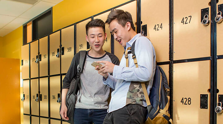 Two Taylors High School students standing by the student lockers.